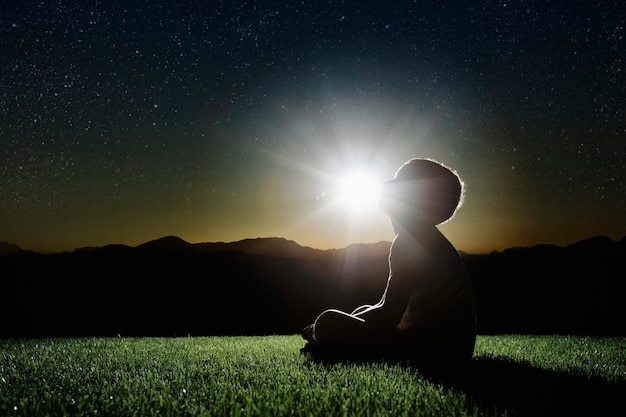 Een kind zit op een bergtop bij zonsondergang en droomt