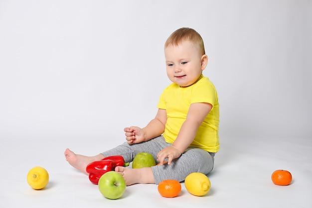 Een kind zit op een witte achtergrond in een gele t-shirt met groenten en fruit