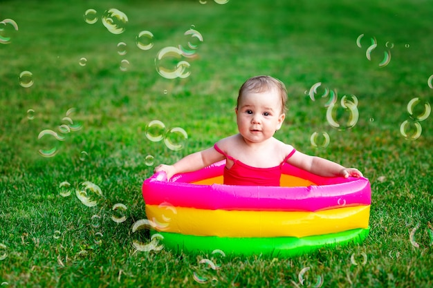 Een kind zwemt in de zomer in een opblaasbaar zwembad op het groene gras met zeepbellen, ruimte voor tekst