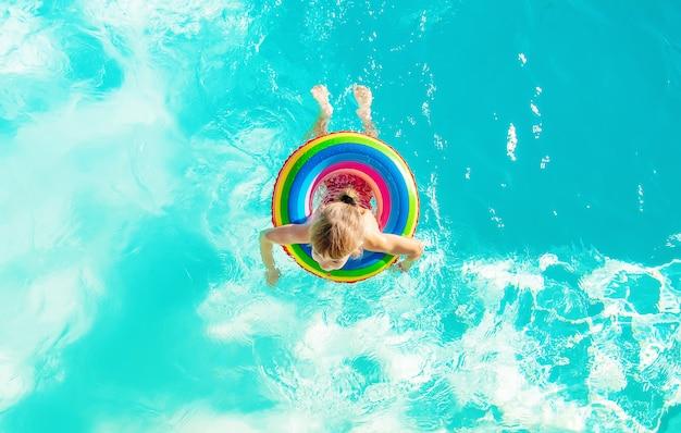 Een kind zwemt in een zwembad met een reddingsboei. selectieve aandacht.