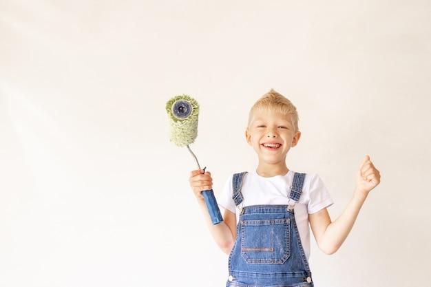 Een kindbouwer in een appartement met witte muren en een roller in zijn handen toont de klas, een plek voor tekst, het concept van reparatie