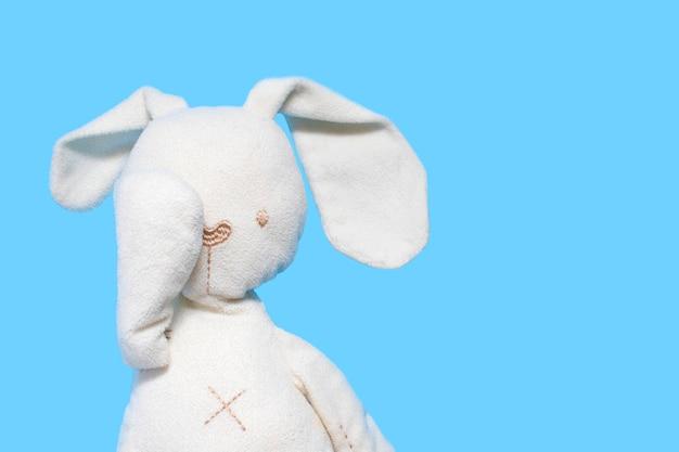 Een kinderspeelgoed, een wit konijn op een blauwe motorkap, bedekt de ogen met een poot. .
