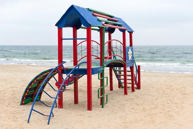 Een kinderspeeltuin voor actieve spelletjes op het strand. kleurrijke lege speeltuin in een park vlakbij de zee. verbetering van openbare ruimtes.