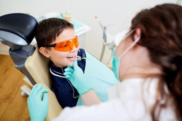 Een kindjong geitje is jongen bij tandarts in tandkantoor. tandheelkundige behandeling