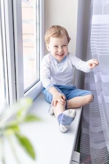 Een kindjongen kijkt uit het raam zittend op de vensterbank van het huis