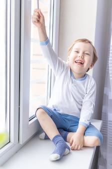 Een kindjongen kijkt uit het raam zittend op de vensterbank van het huis.