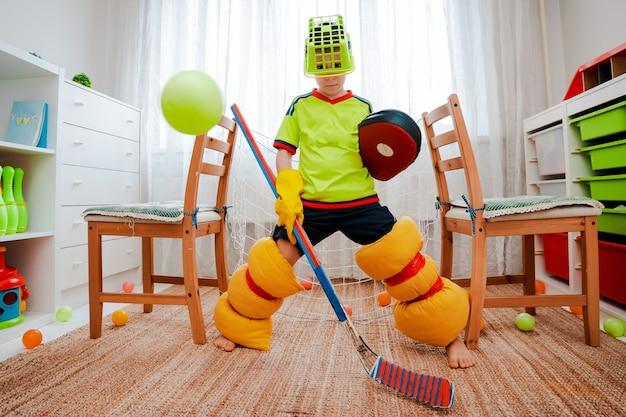 Een kindjongen speelt thuis hockey