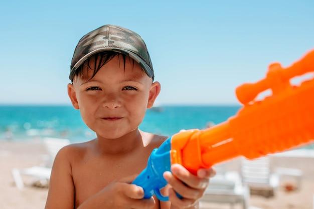 Een kindjongen staat in de buurt van de zee met een close-upportret van een waterpistool. waterspelletjes van kinderen in de buurt van het water op het strand. hoge kwaliteit foto