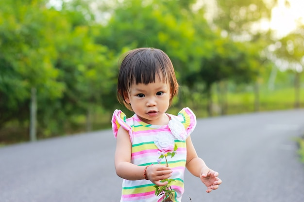 Een kindmeisje die en een gras bevinden zich houden bloeit in haar handen bij het natuurreservaat.