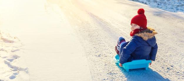 Een kindmeisje glijdt van een heuvel af in de sneeuw