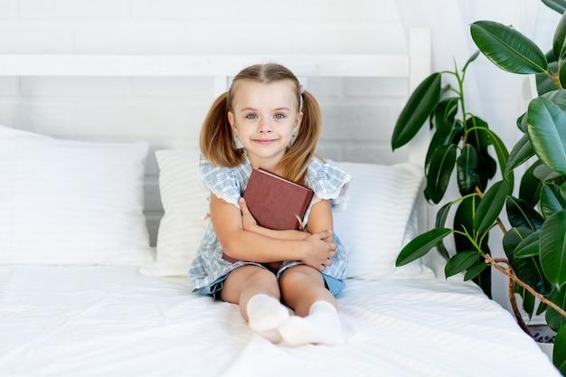 Een kindmeisje houdt thuis een boek op het bed op een wit katoenen bed en glimlacht liefjes
