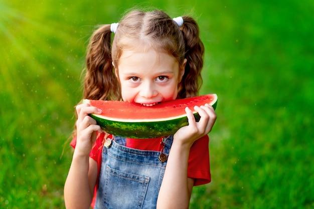Een kindmeisje in de zomer op het gazon met een stuk watermeloen op het groene gras heeft plezier en verheugt zich erop te bijten, ruimte voor tekst
