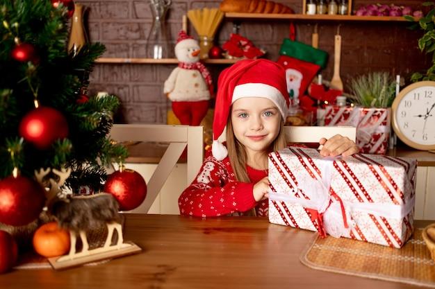 Een kindmeisje in een kerstmuts met geschenken in een donkere keuken bij een kerstboom met rode ballen verheugt zich en glimlacht, het concept van nieuwjaar en kerstmis
