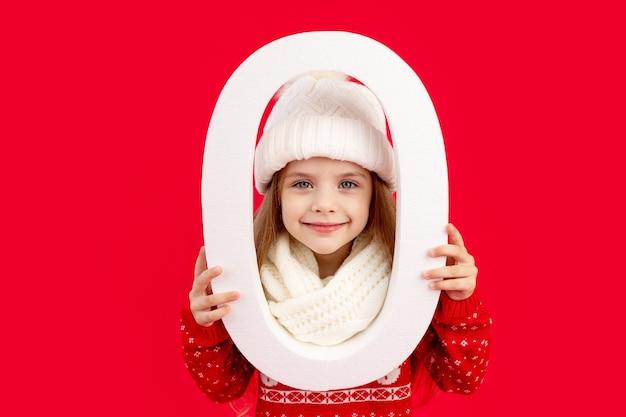 Een kindmeisje in een wintermuts en trui met een groot getal nul op een rode monochrome geïsoleerde achtergrond verheugt zich en glimlacht, het concept van nieuwjaar en kerstmis, ruimte voor tekst