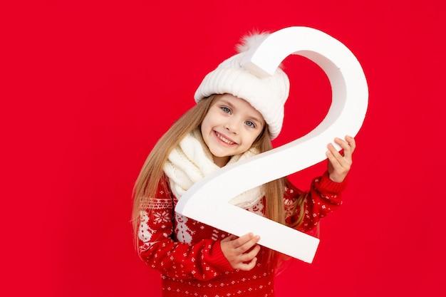 Een kindmeisje in een wintermuts en trui met een groot nummer twee op een rode monochrome geïsoleerde achtergrond verheugt zich en glimlacht, het concept van nieuwjaar en kerstmis, ruimte voor tekst
