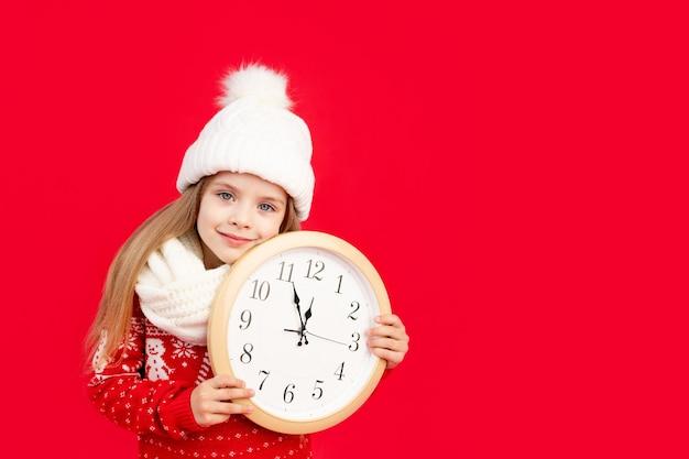 Een kindmeisje in een wintermuts en trui met een grote klok op een rode monochrome geïsoleerde achtergrond verheugt zich en glimlacht, het concept van nieuwjaar en kerstmis, ruimte voor tekst