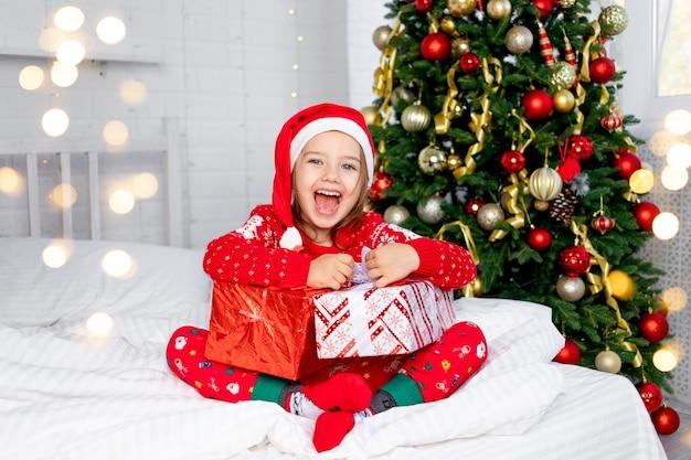 Een kindmeisje met cadeaus bij de kerstboom in een rode trui en kerstmanhoed op oudejaarsavond of kerst thuis op een wit bed schreeuwt van geluk