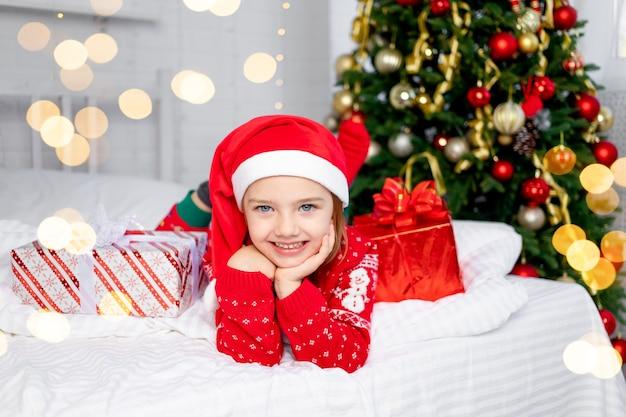 Een kindmeisje met cadeaus bij de kerstboom in een rode trui en kerstmanhoed op oudejaarsavond of kerstmis ligt thuis op een wit bed glimlachend