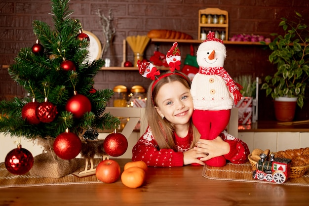 Een kindmeisje met een sneeuwpop in een donkere keuken bij een kerstboom met rode ballen verheugt zich en glimlacht, het concept van nieuwjaar en kerstmis