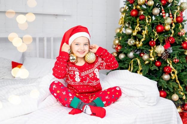 Een kindmeisje met kerstballen op haar oren bij de kerstboom in een rode trui en kerstmanhoed op oudejaarsavond in een wit bed glimlachend en lachend