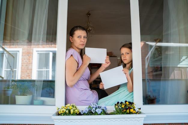 Een kindmeisje met moedervrouw uit het raam toont een wit blanco vel voor een bericht met een kopieerruimte tijdens de thuisisolatie van de coronaviruspandemie