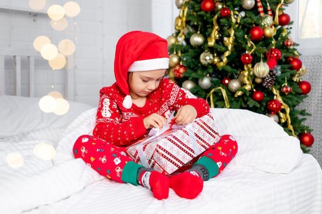 Een kindmeisje pakt geschenken uit bij de kerstboom in een rode trui en kerstmanhoed op oudejaarsavond of kerstmis thuis op een wit bed glimlachend