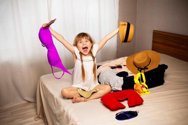 Een kindmeisje schreeuwt van geluk van het nieuws dat ze op vakantie gaat, rust naar de zee tijdens een reis, bereidt kleding, badkleding en paspoorten, hoeden en accessoires voor vreugde en plezier