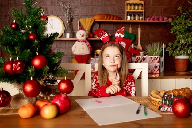 Een kindmeisje schrijft een brief aan de kerstman in een donkere keuken onder een kerstboom met rode ballen, het concept van nieuwjaar en kerstmis