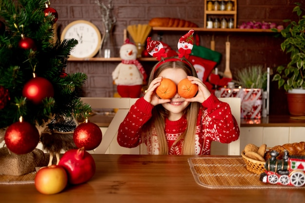 Een kindmeisje verwent zich met mandarijnen die haar gezicht ermee bedekken in een donkere keuken in de buurt van een kerstboom met rode ballen, het concept van nieuwjaar en kerstmis