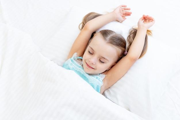 Een kindmeisje werd 's ochtends wakker op het bed thuis op een wit katoenen bed en strekt zich lieflijk uit met een glimlach