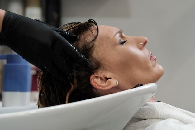 Een klant bij de schoonheidssalon die haar haar wast