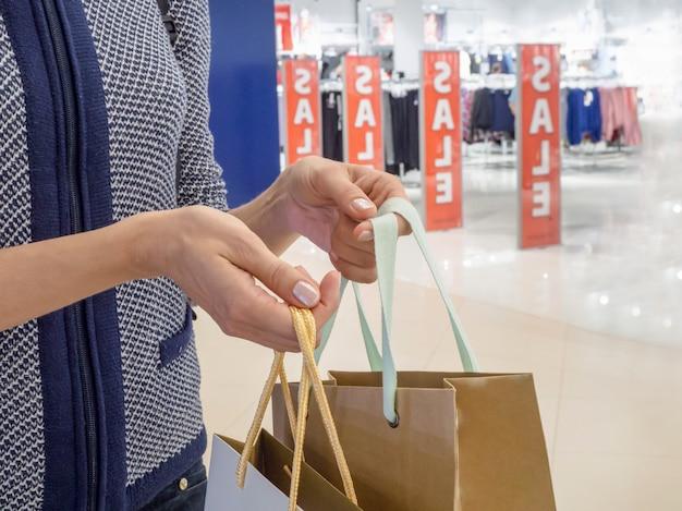 Een klant met tassen in de hand in de winkel.