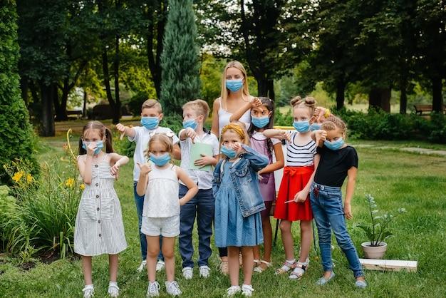 Een klas gemaskerde schoolkinderen volgt tijdens de epidemie buitentrainingen. terug naar school, leren tijdens de pandemie.