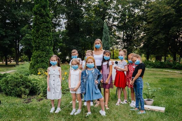 Een klas gemaskerde schoolkinderen volgt tijdens de epidemie buitentrainingen