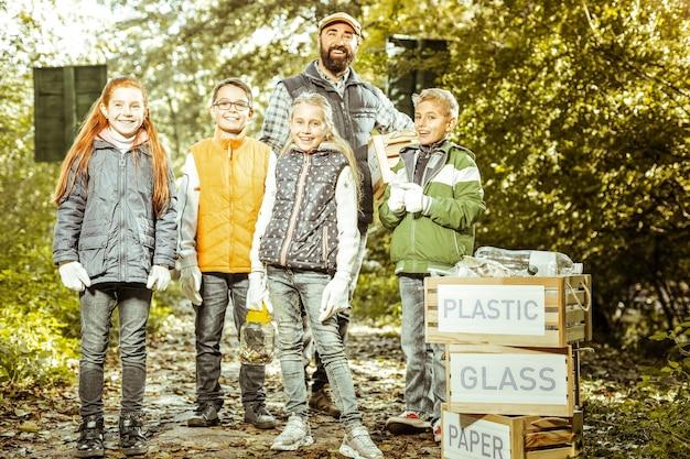 Een klas met een leraar die poseert na het schoonmaken en het sorteren van afval in het bos op een goede dag