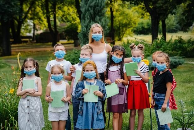 Een klas van gemaskerde schoolkinderen is bezig met buitentraining tijdens de epidemie