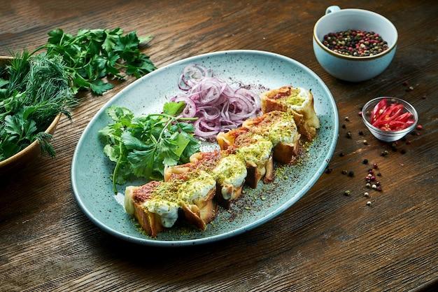 Een klassiek turks gerecht is gesneden shoarma met kipkebab gegarneerd met rode en witte pistachesaus, geserveerd in een blauw bord op een houten tafel. restaurant eten