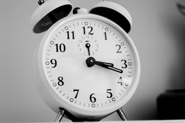Een klassieke desktop-wekker in zwart-witfotografie