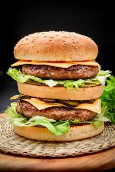 Een klassieke dubbele cheeseburger met twee runderpasteitjes, saus, sla, kaas, augurken en uien op een sesambroodje