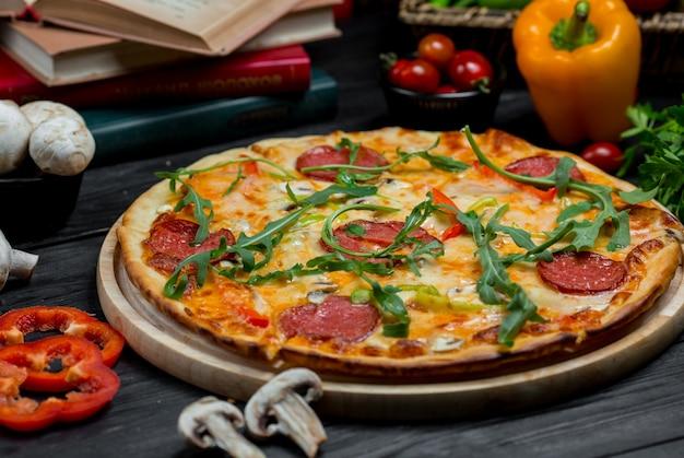 Een klassieke pepperonipizza met fijngesmolten kaas en groen bovenop