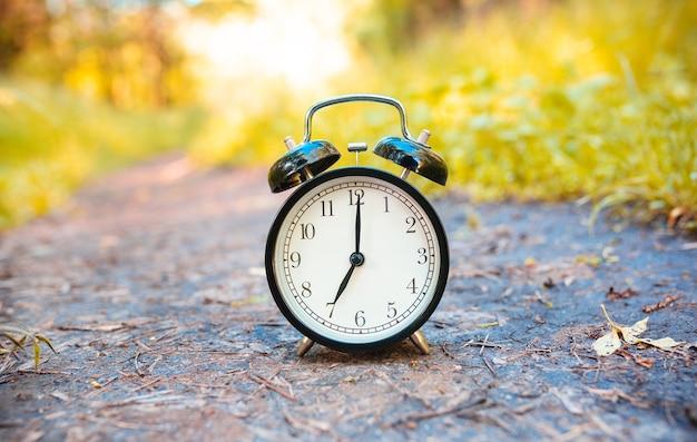 Een klassieke wekker in het bos geeft zeven uur aan