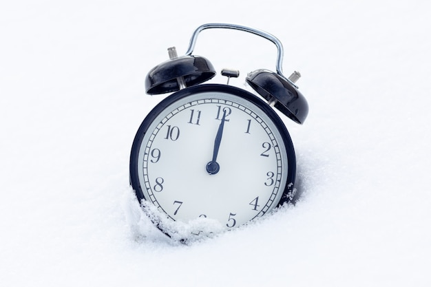 Een klassieke zwarte wekker in de sneeuw. nieuwjaar concept. de tijd is 12 uur op de klok.
