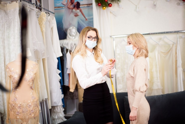 Een kleermaker werkt met een klant in zijn atelier tijdens de pandemie van het coronavirus en draagt beschermende maskers op hun gezicht.