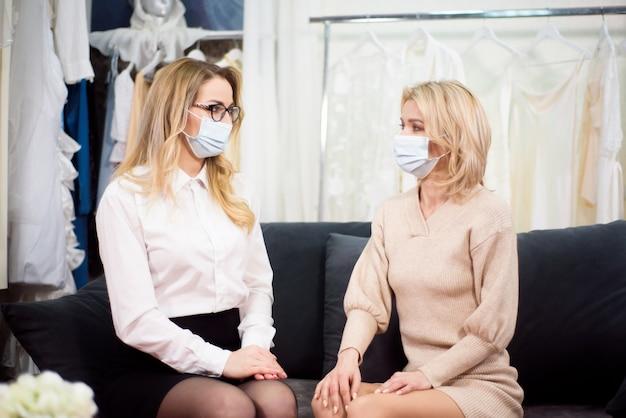 Een kleermaker werkt samen met een klant in zijn atelier tijdens de coronaviruspandemie, met beschermende maskers op hun gezicht.