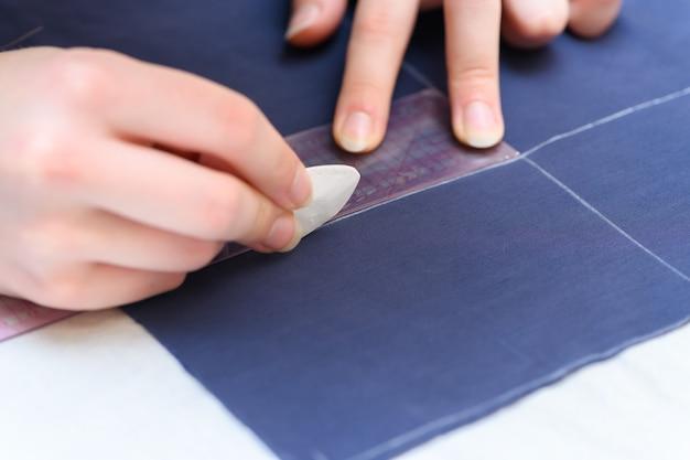Een kleermakershand markeert de lijn op de stof met krijt om een kledingstuk te knippen