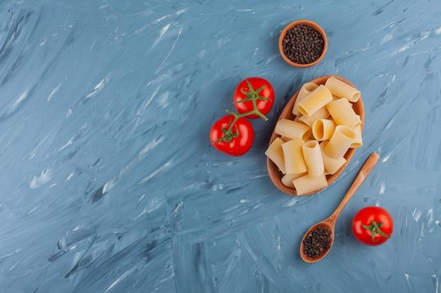 Een kleibord van droge ruwe buisdeegwaren met verse rode tomaten en peperkorrels.