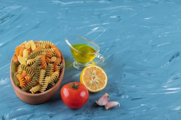 Een kleibord van rauwe pasta met olie en verse rode tomaten op een blauwe achtergrond.
