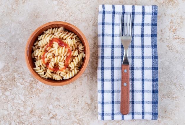 Een kleikom heerlijke pasta op een marmeren ondergrond