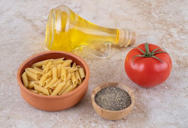 Een kleikom met rauwe macaroni en een glazen fles olie