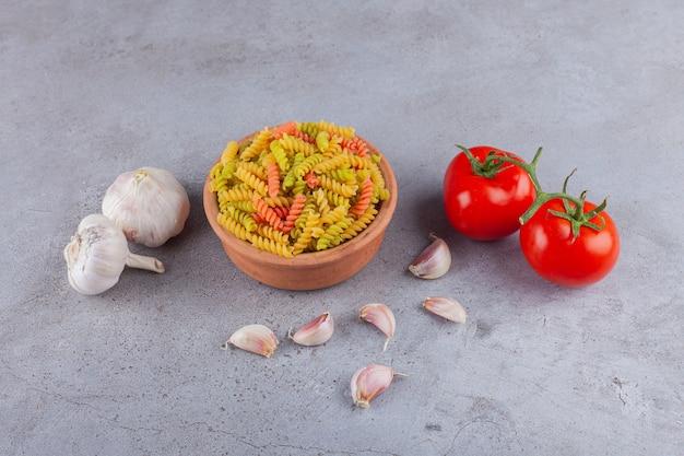Een kleikom van multi gekleurde ruwe spiraalvormige deegwaren met knoflook en verse rode tomaten.